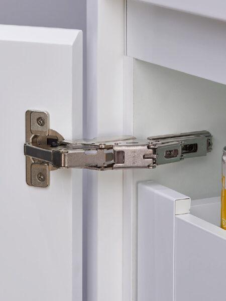 Detalle de apertura de puerta de mueble de cocina con bisagra