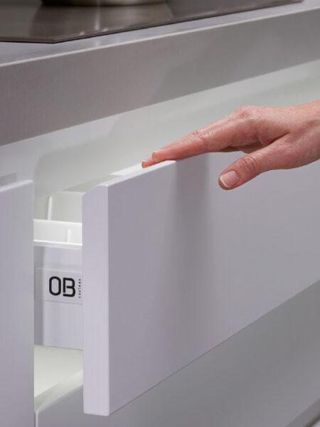 Detalle de apertura de puerta de cajón de cocina de extracción