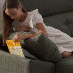 Detalle de niña guardando libro en brazo de sofá cama 10e-0008 color verde